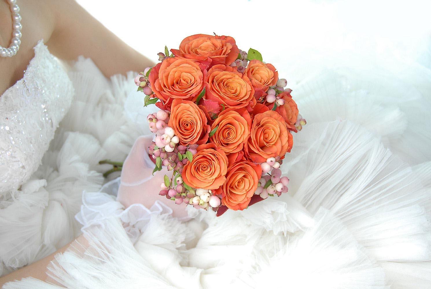 Bouquet de mariage orange tenue par la mariee sur sa robe
