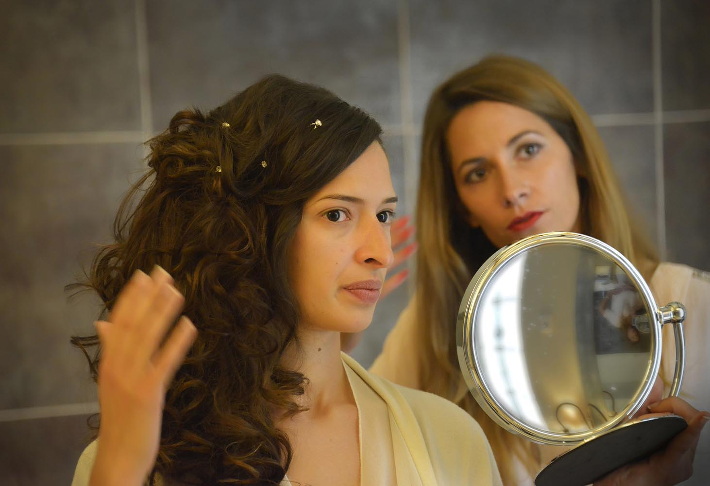 Bride and hairdresser admiring hairstyle in front of mirror