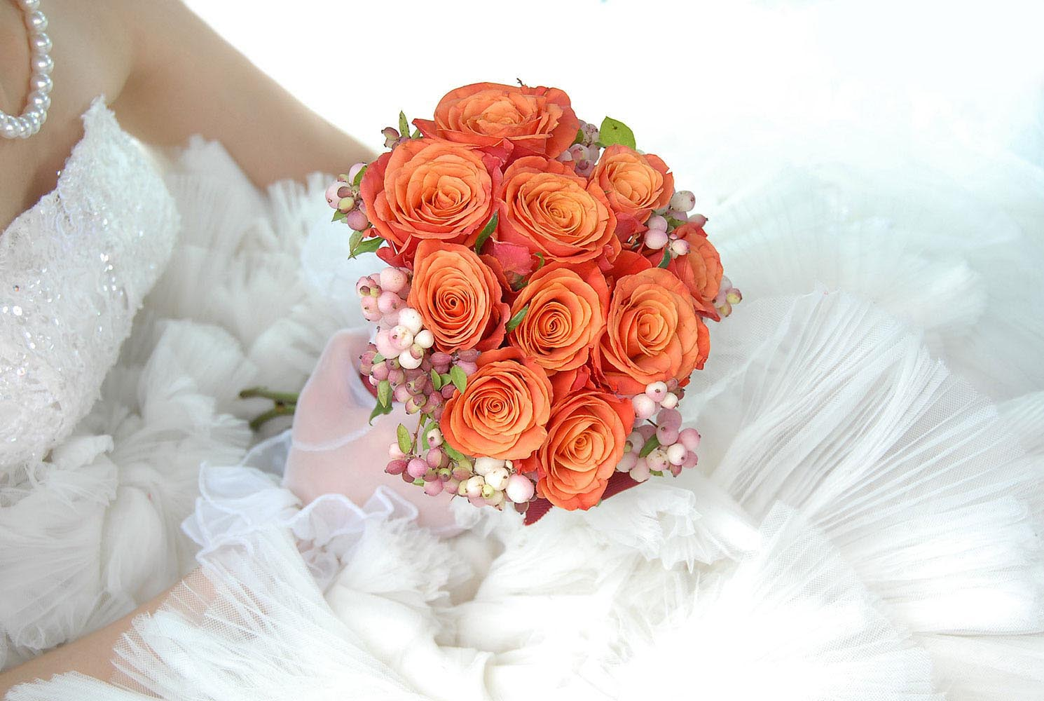 Orange wedding bouquet held by bride in dress and pearl necklace