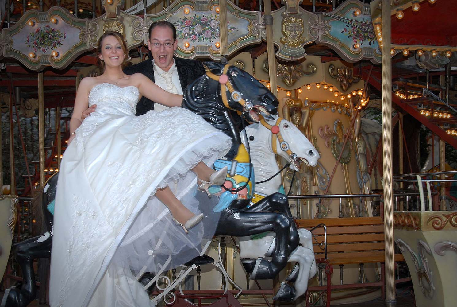 Groom and bride in wedding dress on merry go round, Paris, France
