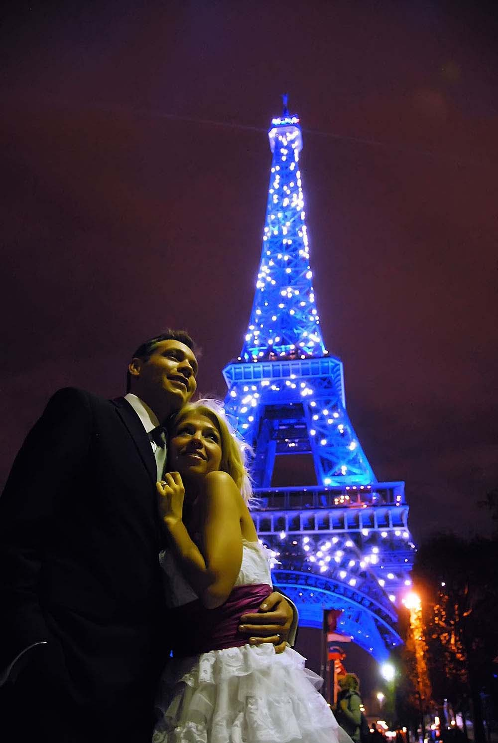 Bride and groom with twinkling blue Eiffel Tower in background, Paris, France
