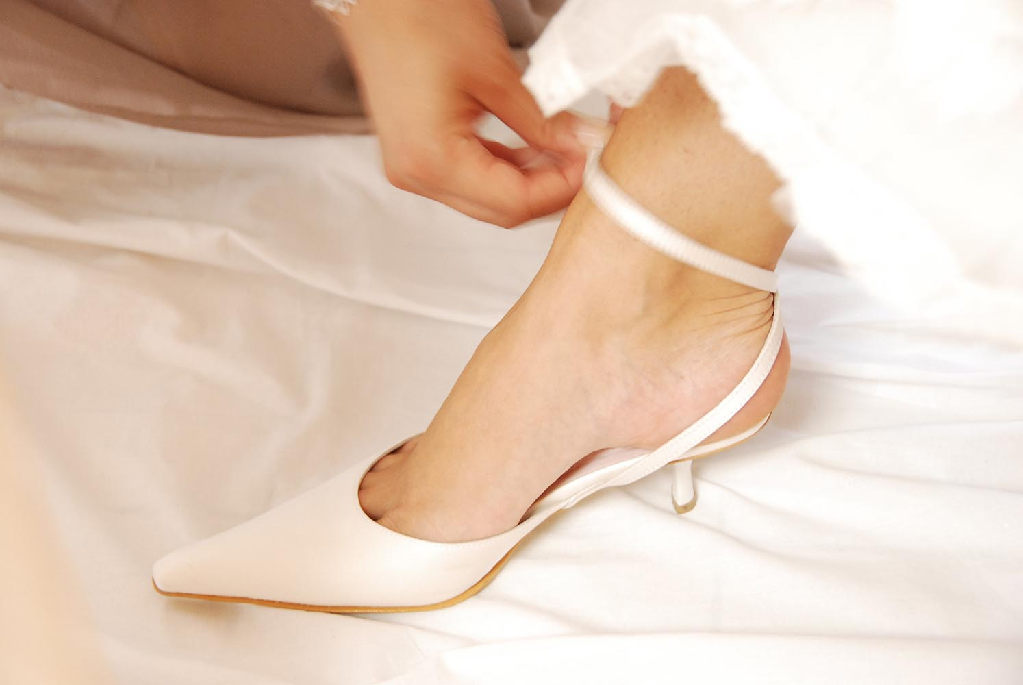 Bride lacing up her white wedding shoe