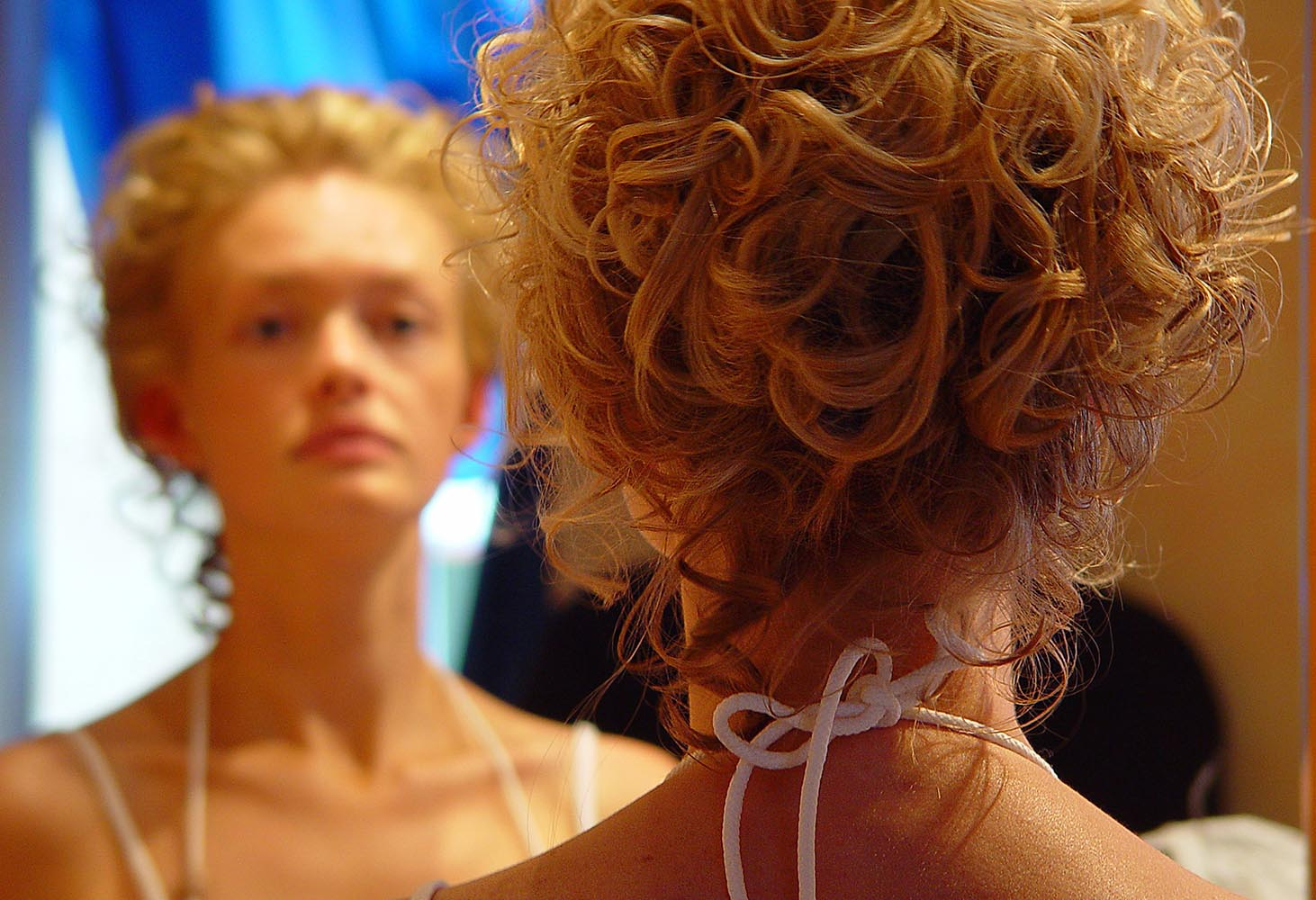 Bride in front of mirror after hairstyling