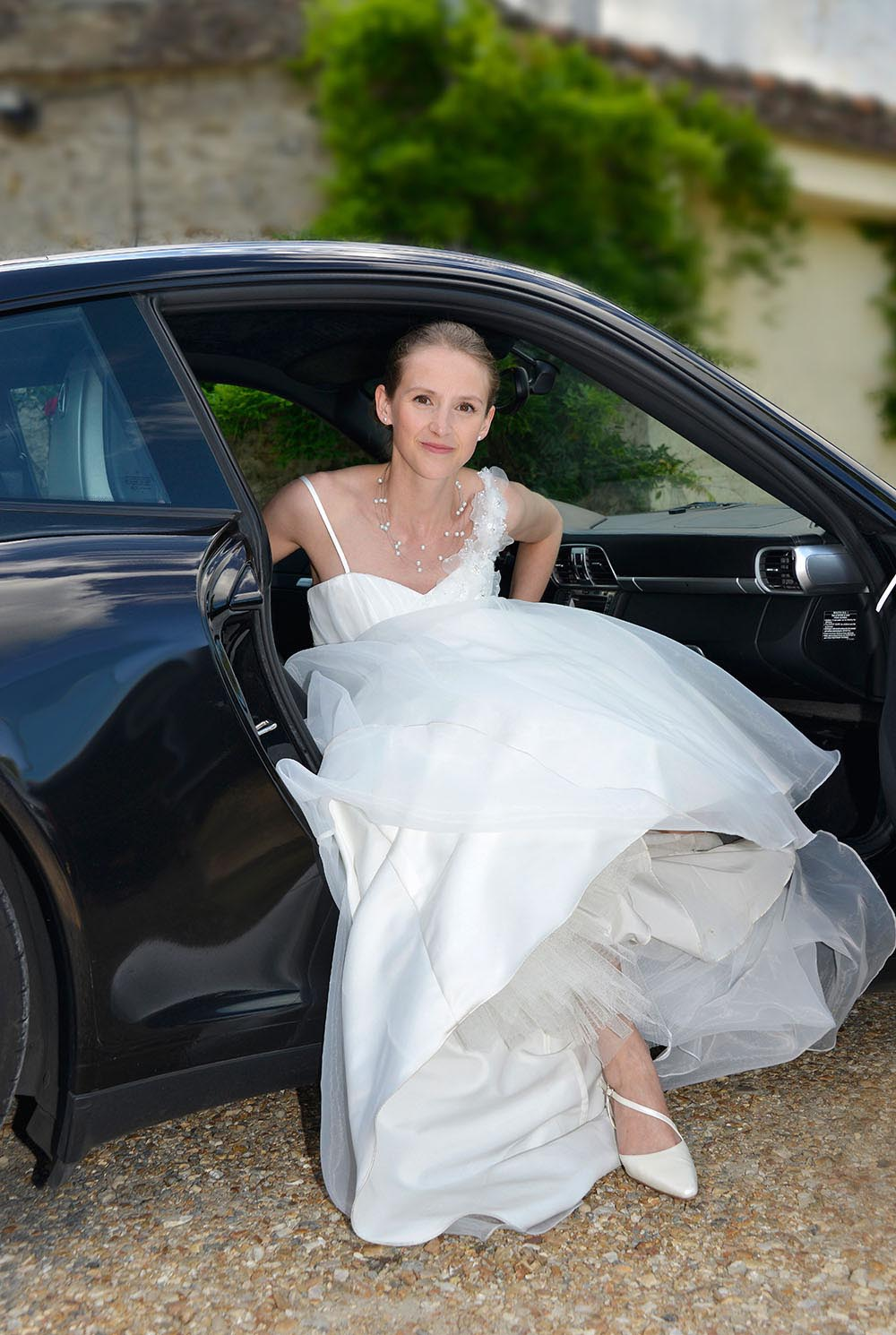 Bride in wedding dress, getting out of car