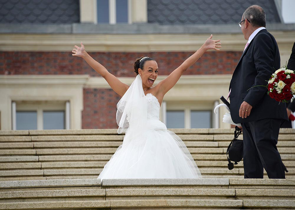 Photo before touching up of a happy Bride in wedding dress showing happiness hands up