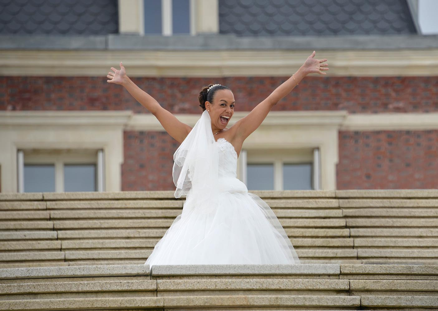Happy Bride in wedding dress showing her happiness with hands up