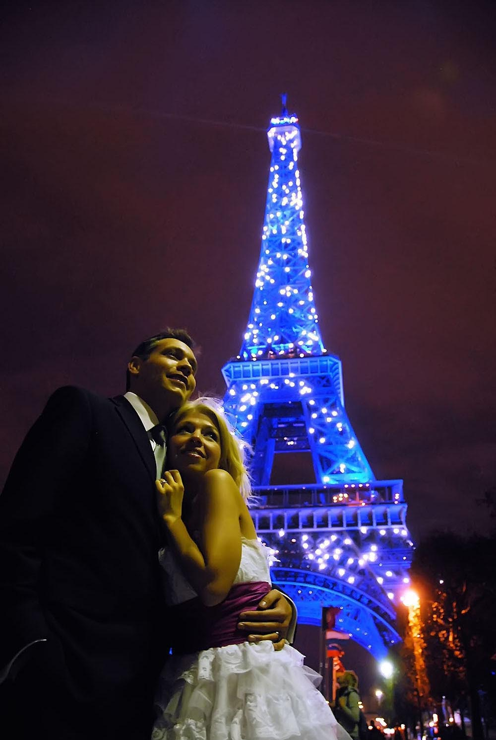 Couple de maries devant la Tour Eiffel bleue et etincellant, Paris