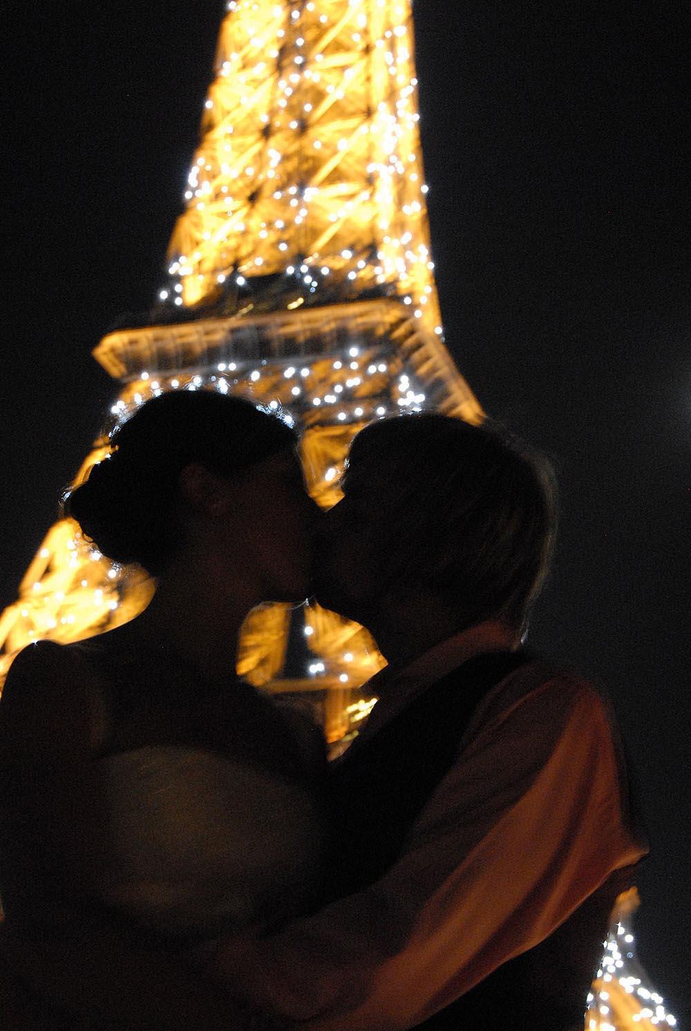 Couple de maries s'embrassant avec la Tour Eiffel illumine de nuit