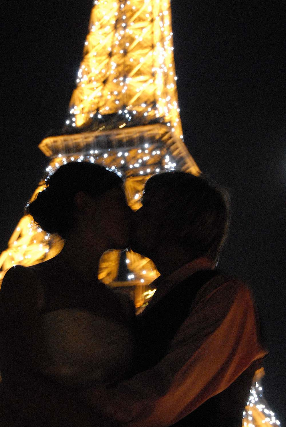 Couple kissing with glittering Eiffel Tower backdrop, Paris, France