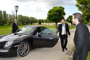 Photo before touching up of groom in front of prestige car