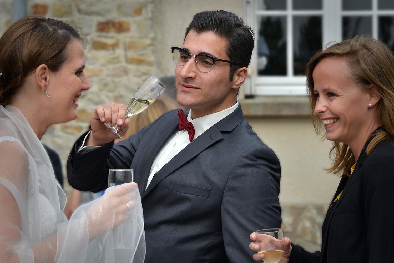 Homme buvant une coupe de champagne avec mariee et invite