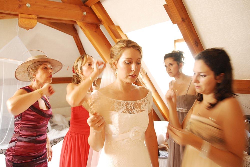 Photo apres retouches de la mariee aidee a s'habiller par les invites du mariage