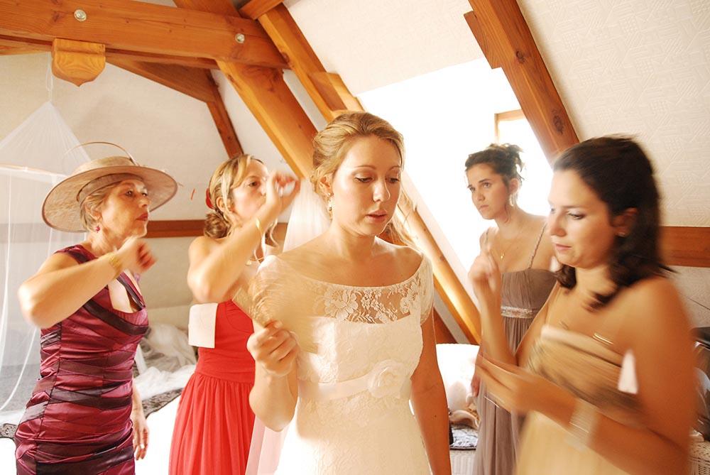 Photo avant retouches de la mariee aidee a s'habiller par les invites du mariage