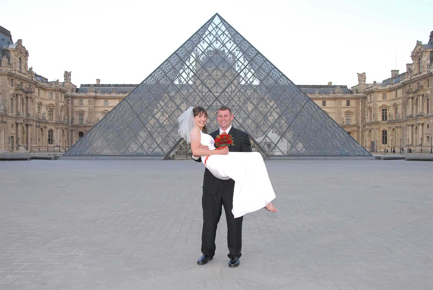 Married couple in front of the Louvre pyramid, Paris, France