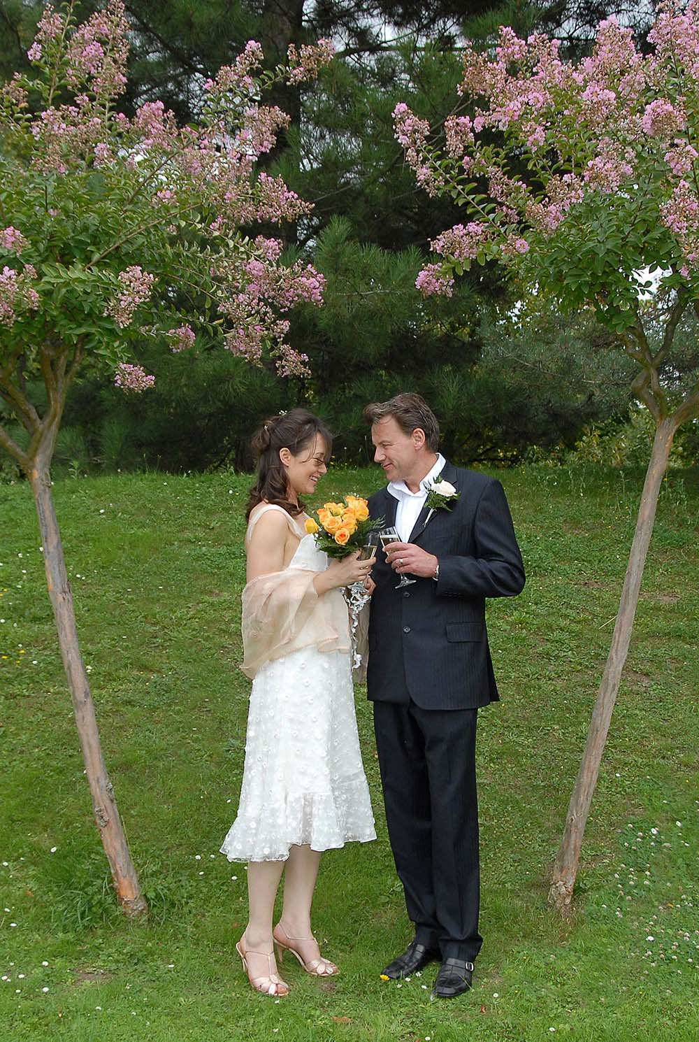 Married couple holding flowers and champagne, Parc Floral, Paris, France