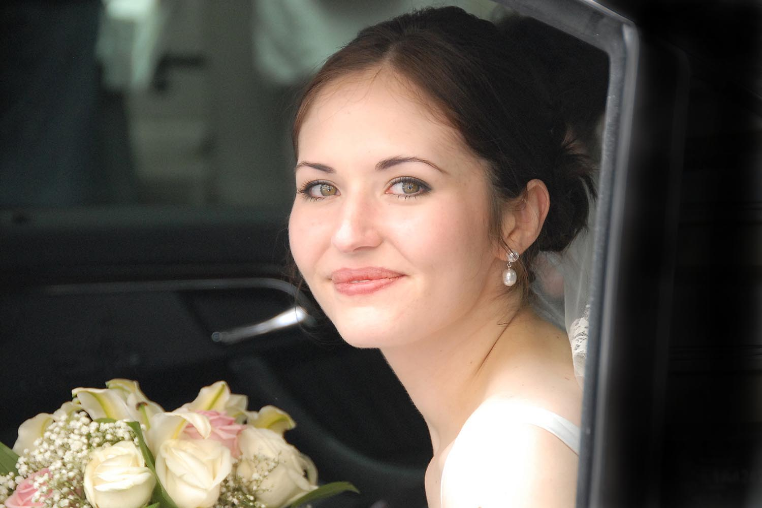 Portrait of bride holding a bouquet of flowers in limousine
