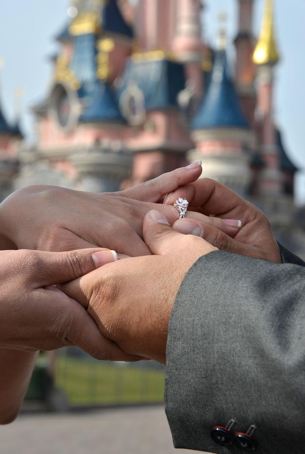 Groom putting engagement ring on bride fingers with EuroDisney backdrop