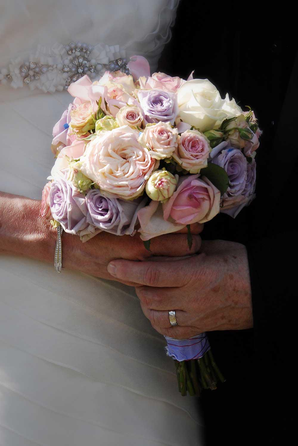 Wedding bouquet held both by bride and groom
