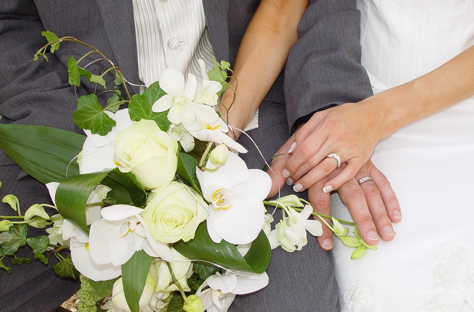 Wedding bouquet with bride and groom hands with rings