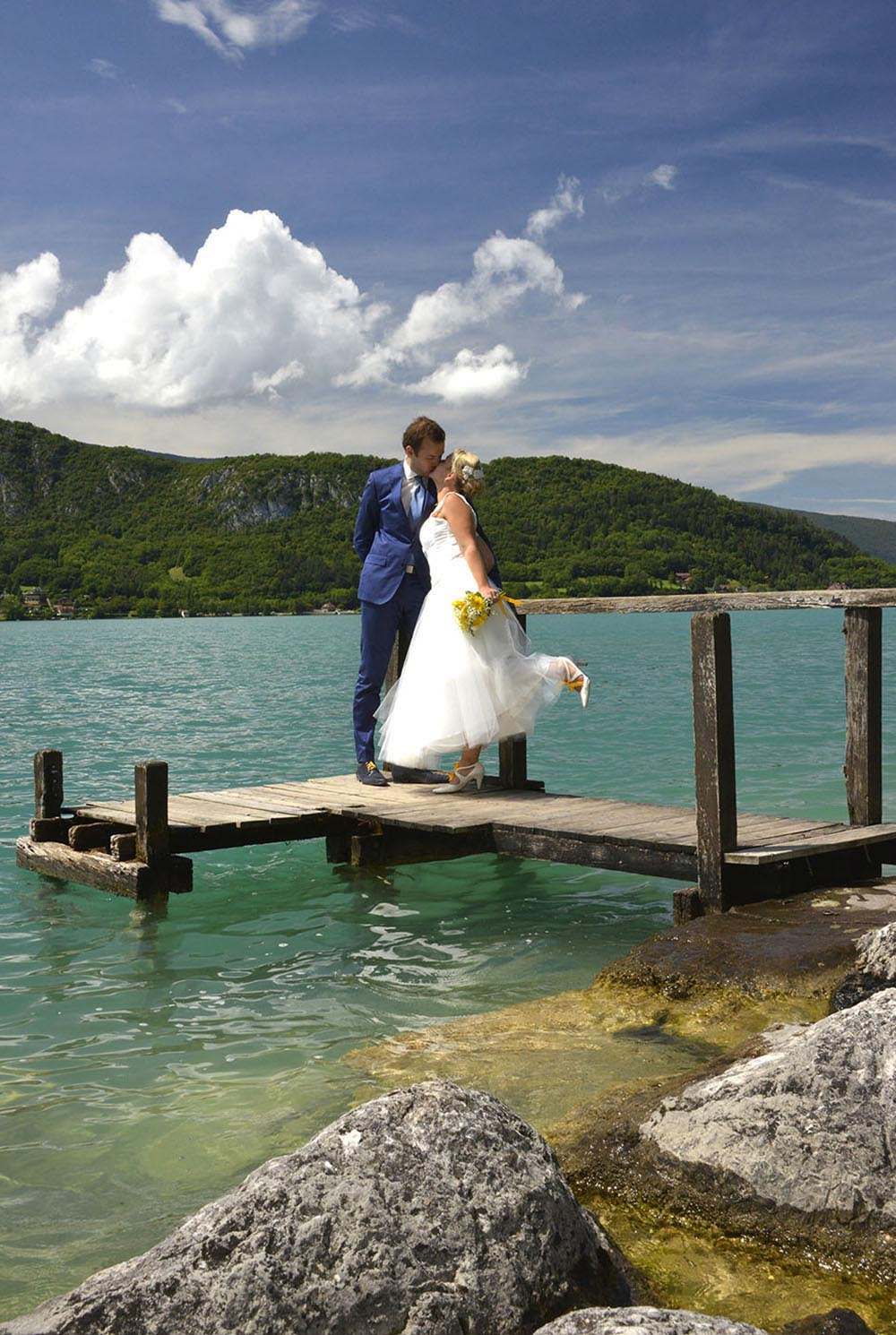 Wedding couple kissing on pontoon, Talloires, Lake Annecy, France