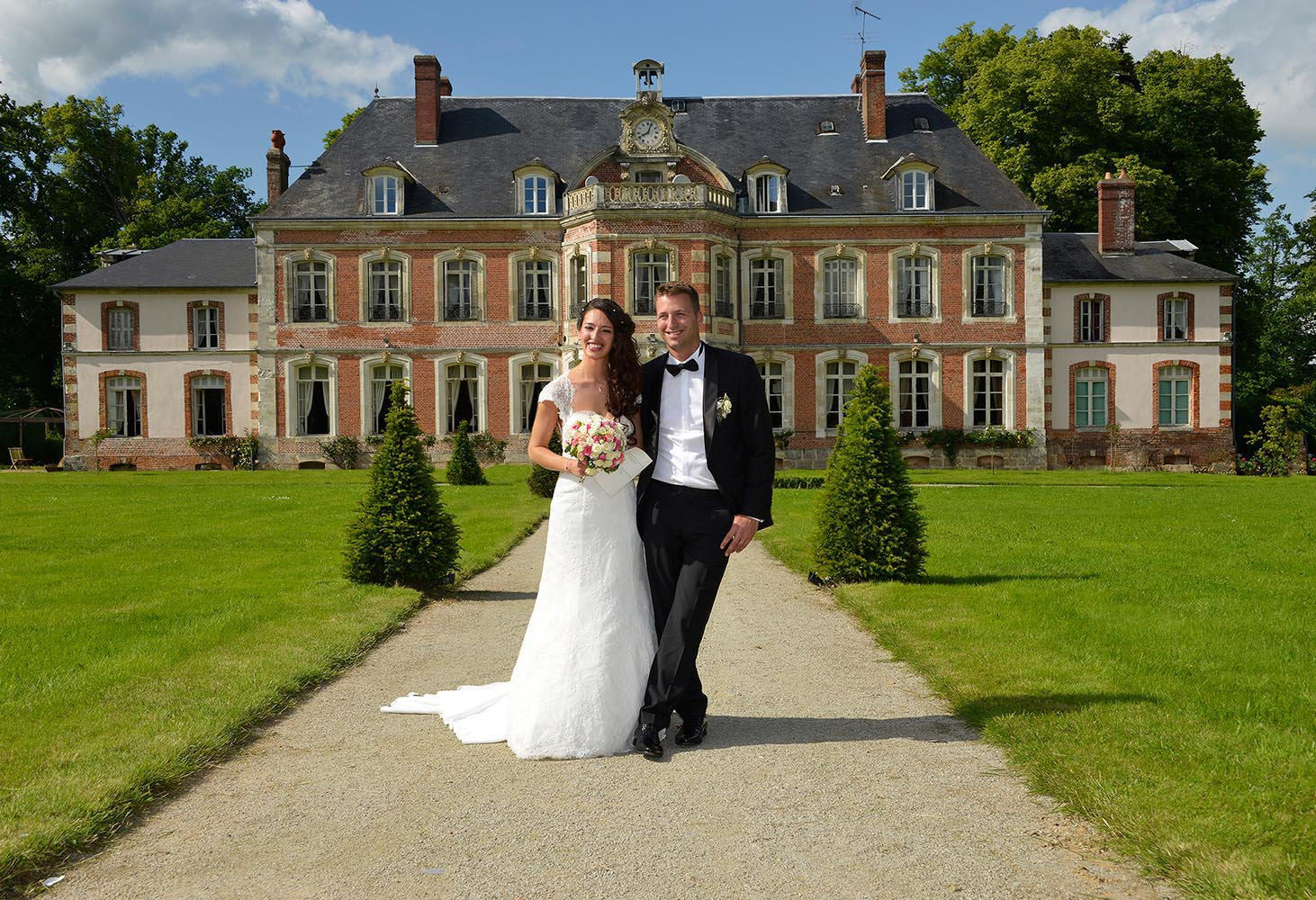 Wedding couple in front of castle at Saint-Leger-de-Rotes, France