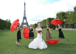 Wedding with bride, guests and red umbrellas, Eiffel Tower gardens, Paris, France
