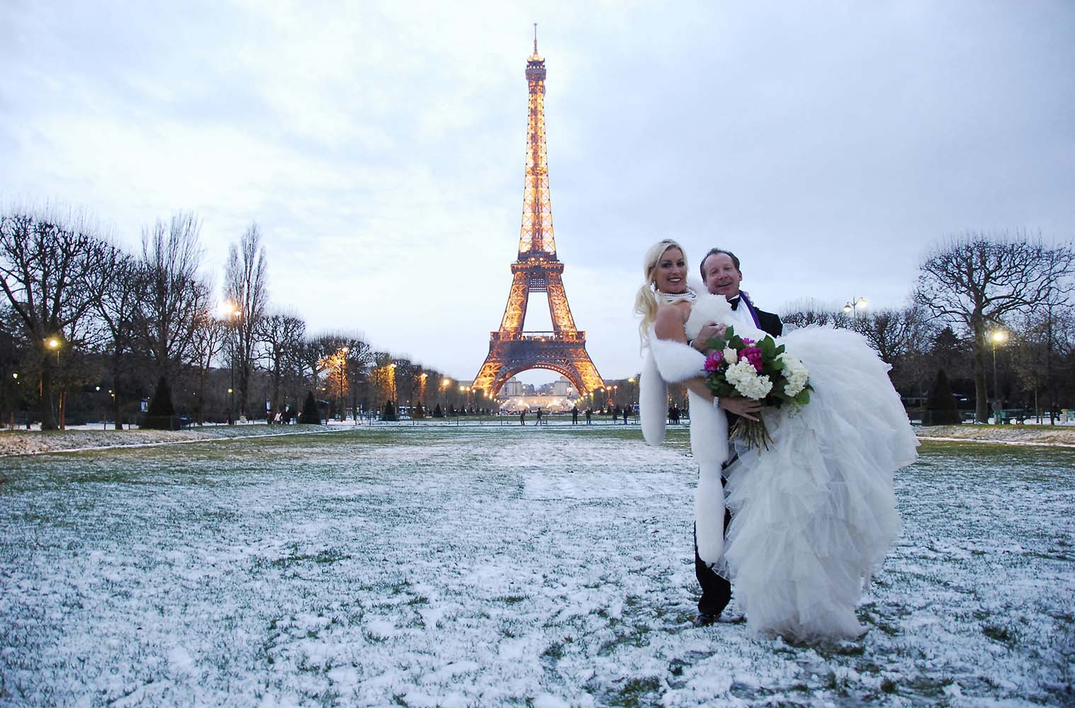 Wedding with bride and groom on snowy Eiffel Tower gardens, Paris, France