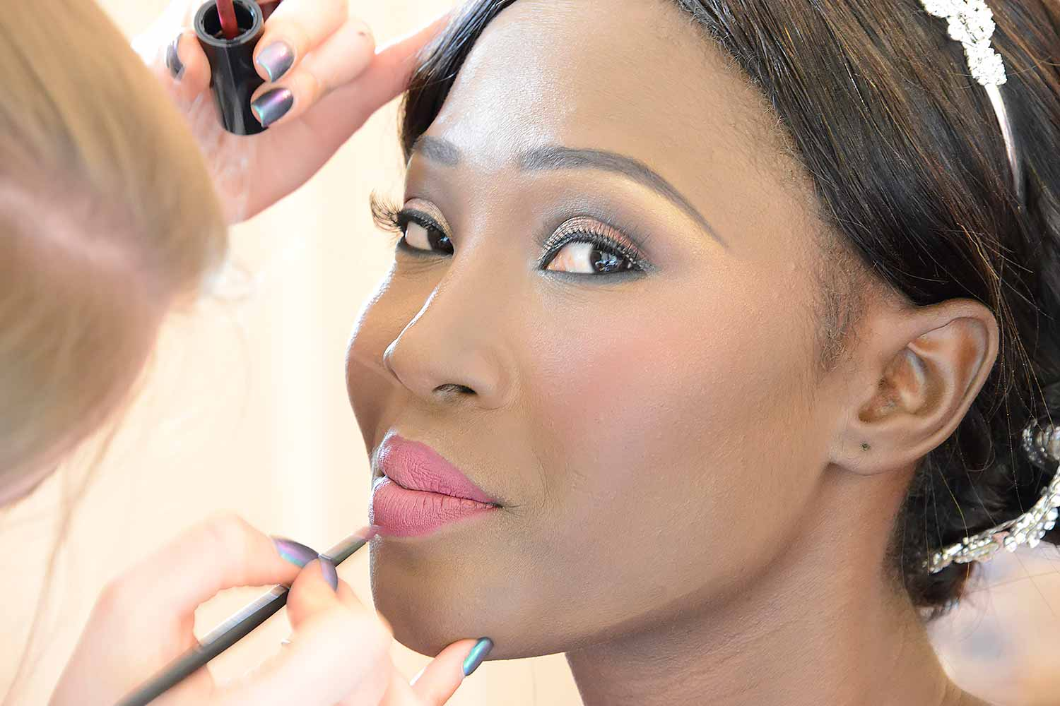 Bride getting her lipstick make-up with a brush