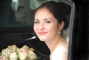 Portrait of bride holding a bouquet of flowers in wedding limousine