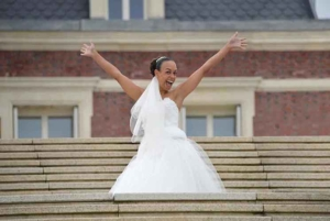 Bride in wedding dress showing her happiness hands up