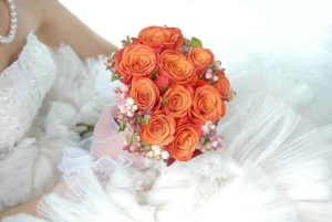 Orange wedding bouquet held by bride in dress and pearl necklace - Photo Haig Wedding Photographer Paris
